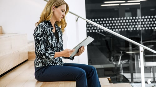 Woman sitting on stairs working on Surface tablet