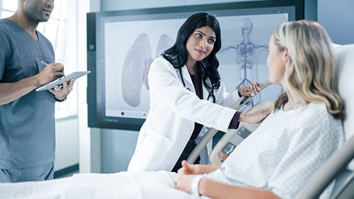 Doctor and patient having conversation, Surface Hub in background
