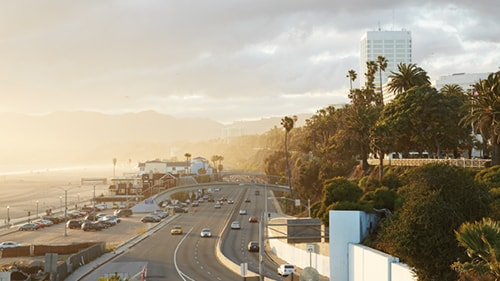 Landscape photo of highway bisecting beach and downtown area