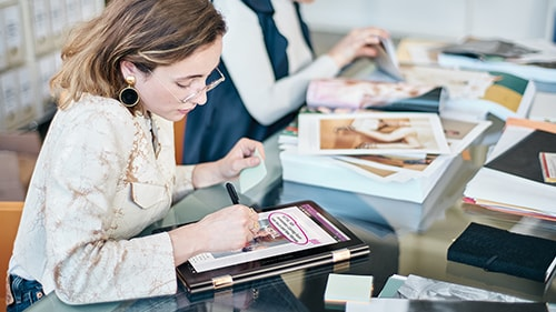 Woman designer working at desk on Surface