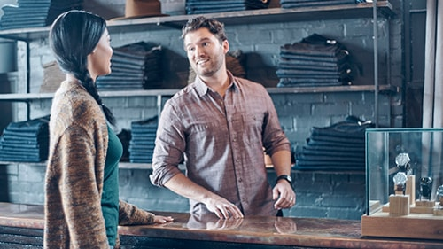 Woman interacting with jeans salesman