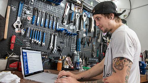 Man working on computer in mechanic shop
