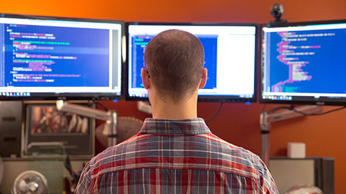 Man sitting at desk with three monitors