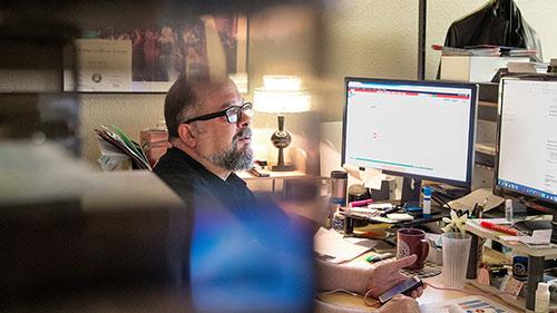 Man sitting at desk working on desktop computer