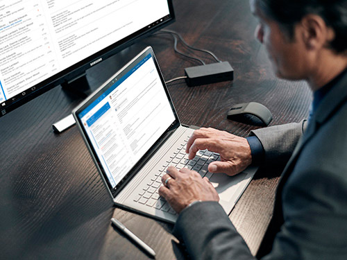 Man at desk working on laptop and desktop computer