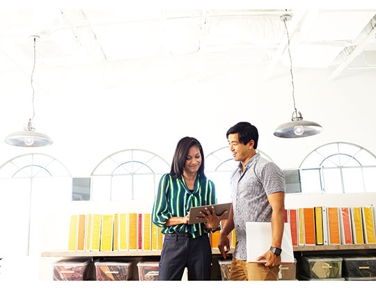 Man and woman looking at a tablet in an office