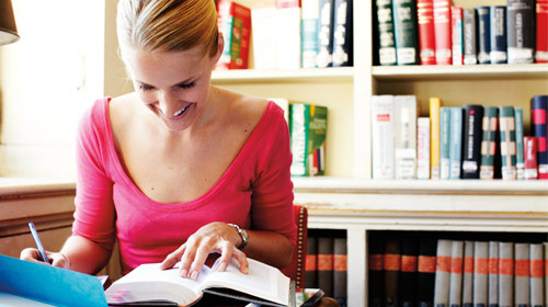 Woman looks at book and tablet