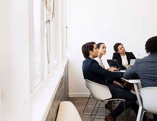 4 coworkers sitting near window having a meeting