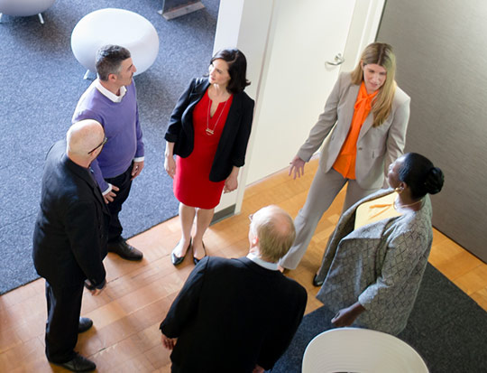Coworkers standing outside conference room chatting
