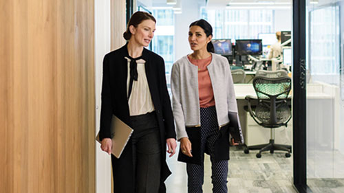 Two women partners walking out of an office