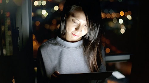Woman looking at tablet at night