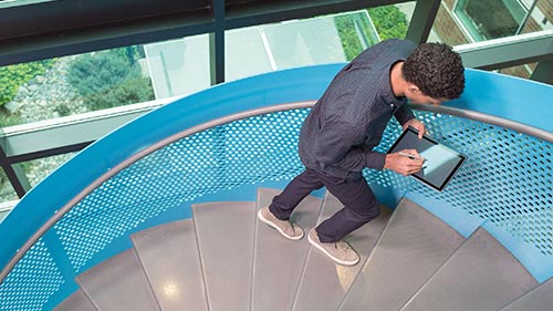 Man climbing stairs while working on tablet