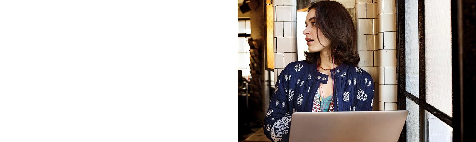 Woman in café with laptop and earbuds