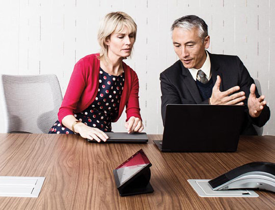 Man and woman looking at information on laptop
