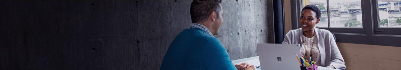 Man and woman at desk conversing