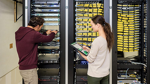 Man and woman working in server room