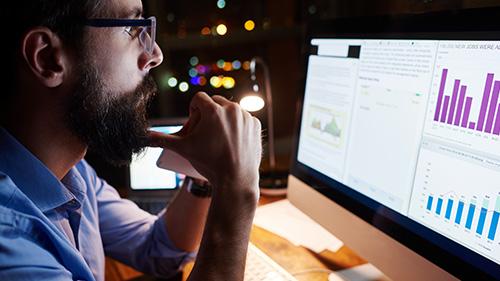 Man viewing data charts on monitor