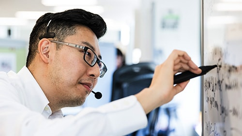 Man with headset writing on whiteboard