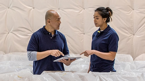Man and woman discussing and pointing to Surface tablet