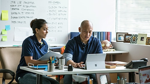 Man and woman working on Surface tablet