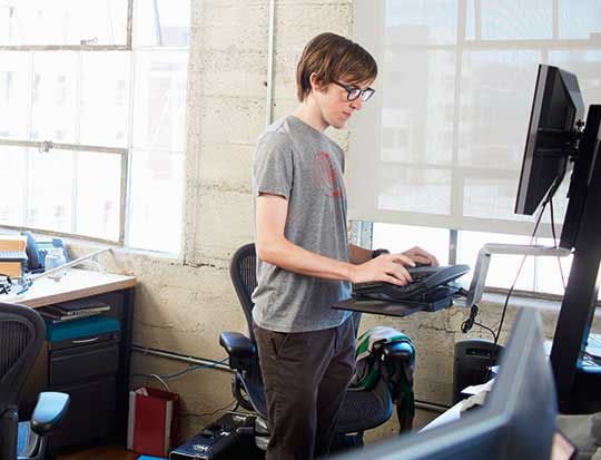 Man standing while working on desktop