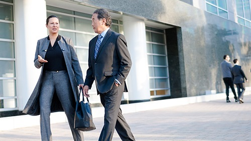 Two coworkers having discussion walking through courtyard