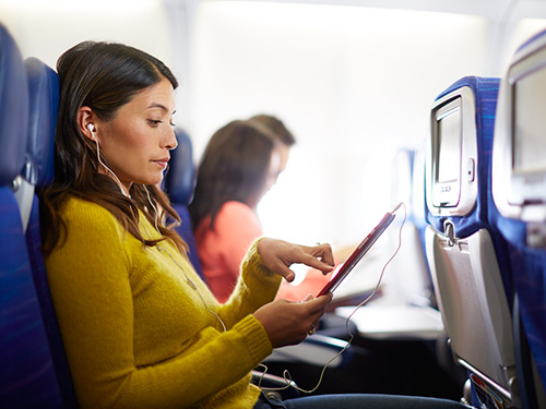Woman traveling on plane and working on tablet