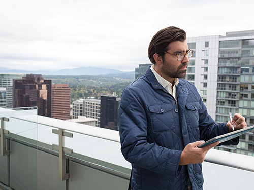 Man standing outside using pen on tablet