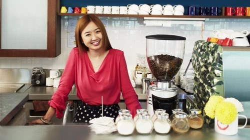 Woman standing behind counter smiling
