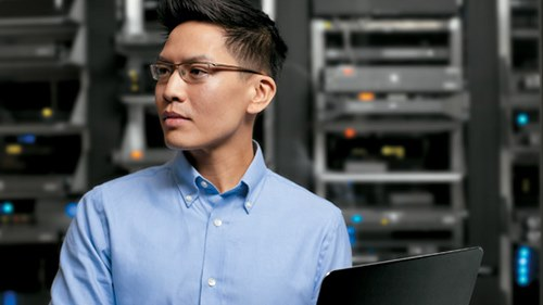 Man standing working on laptop computer