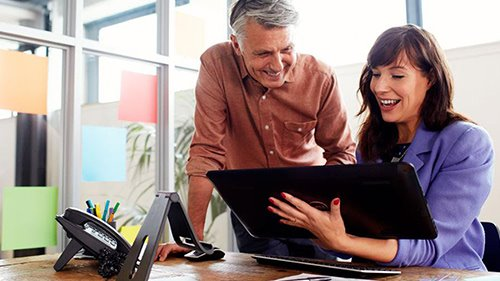 Two coworkers working on tablet and smiling