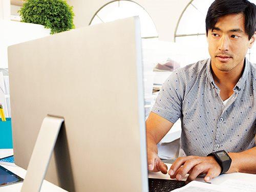 Man typing while working on desktop computer