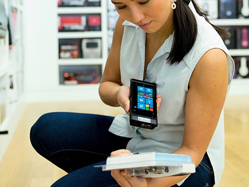 Woman scanning product with smartphone