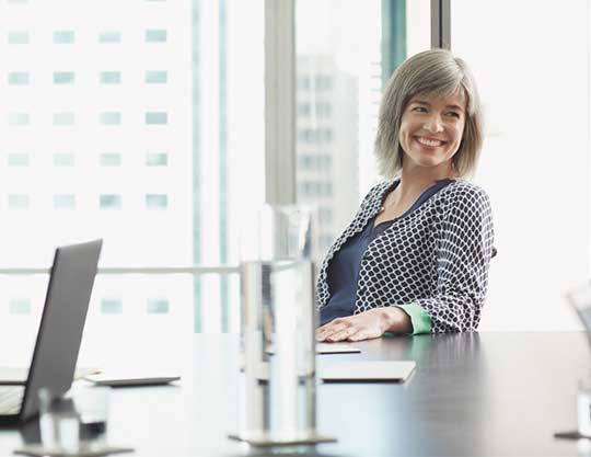 Woman smiling while sitting at conference table