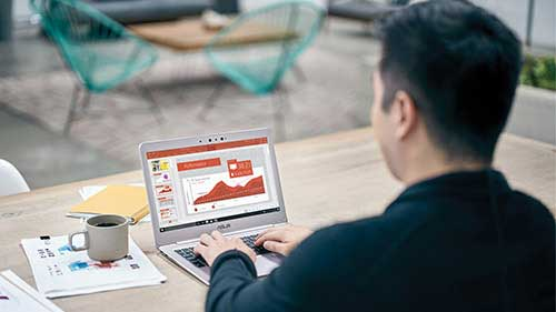 Man sitting at desk while working on laptop