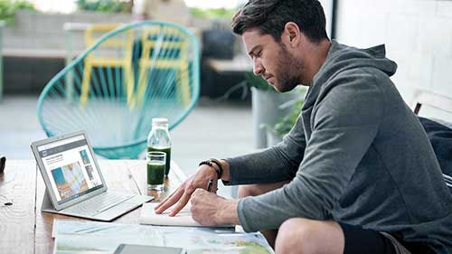 Man writing in notebook with open Surface on the table