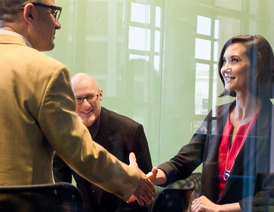 Coworkers during meeting in conference room shaking hands