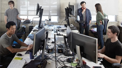 Five colleagues sitting and standing in computer terminal