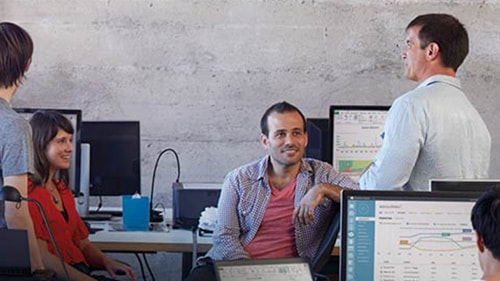 Coworkers sitting in front of computers, talking and laughing