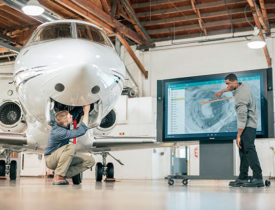 Man working on Surface Hub and another man working on airplane nearby