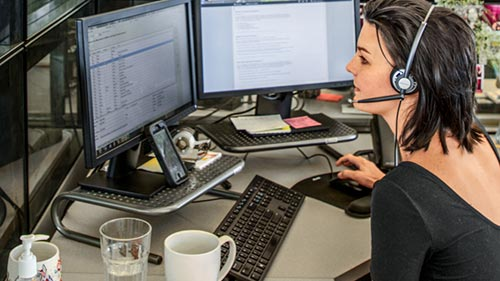 Woman with headset working at desk