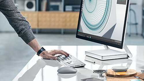 Surface Studio sitting on a desk with hand typing on keyboard