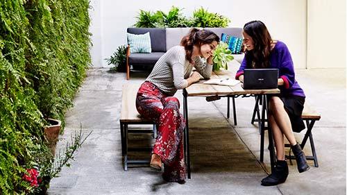 Two women sitting outside working on laptop