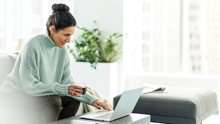 Woman holding a glass working on Surface laptop from home