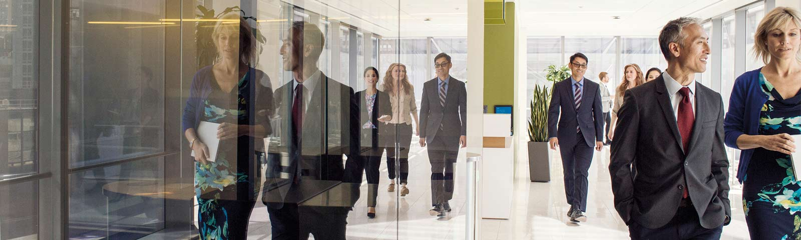 Coworkers walking down hallway, glass showing reflections