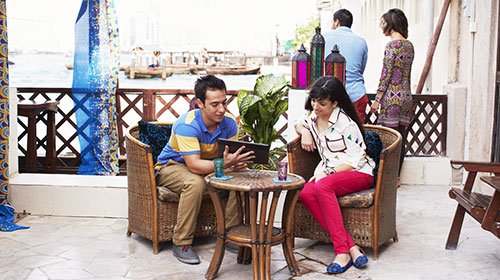 Two people seated on plush chairs looking at a tablet.