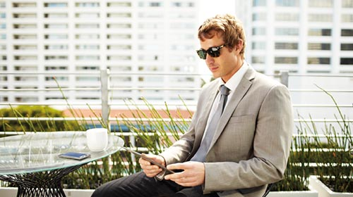 Man in Suit sits on rooftop patio