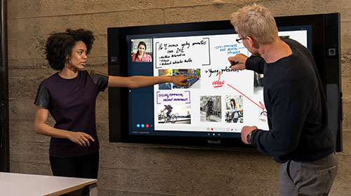 Two people at a writing on a Microsoft Surface Hub.