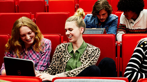 Two women sitting in an auditorium at a laptop.