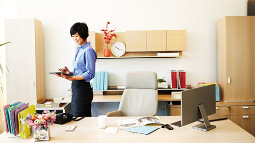 Woman standing behind desk looking at tablet
